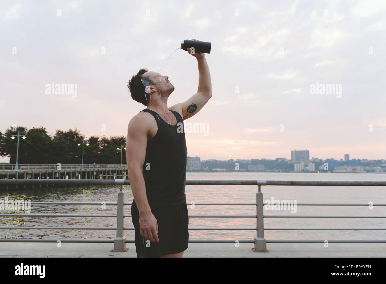 Young male runner pouring water over his face on riverside at sunrise - Stock Image
