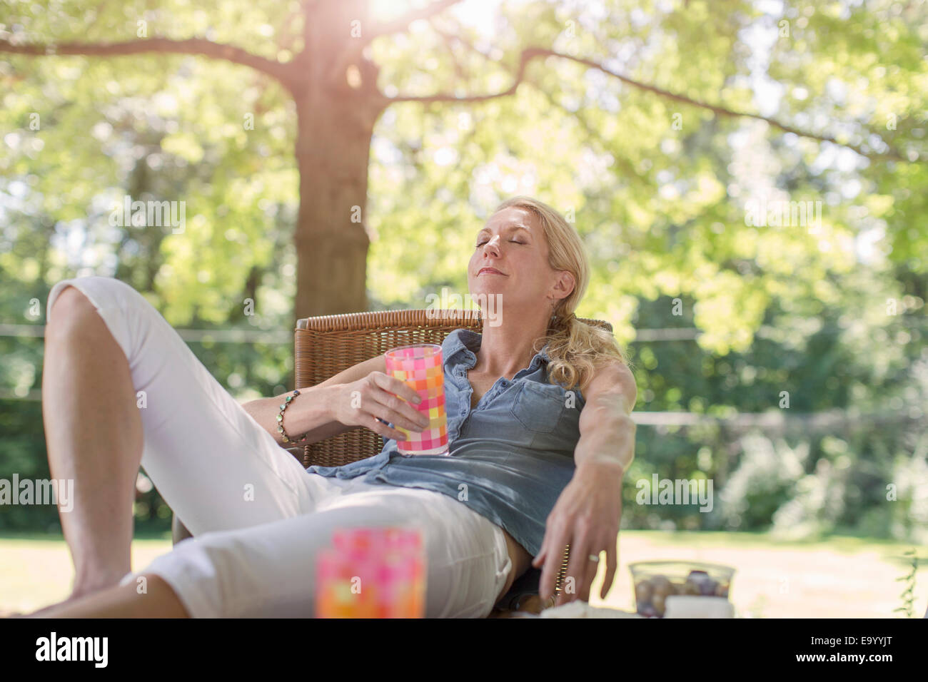 Mature woman relaxing in garden with drink - Stock Image