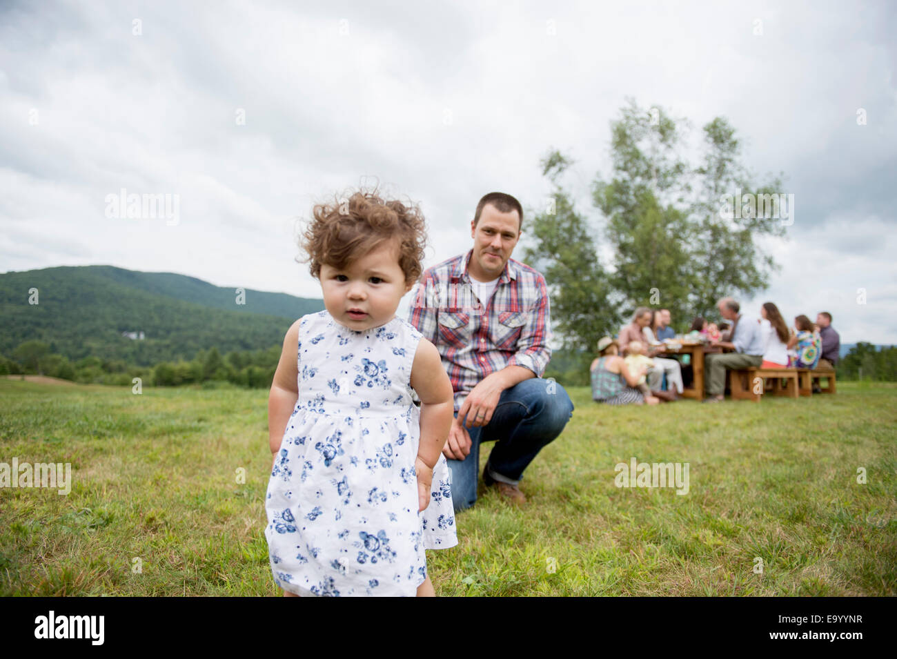 Father playing with daughter at family gathering, outdoors - Stock Image
