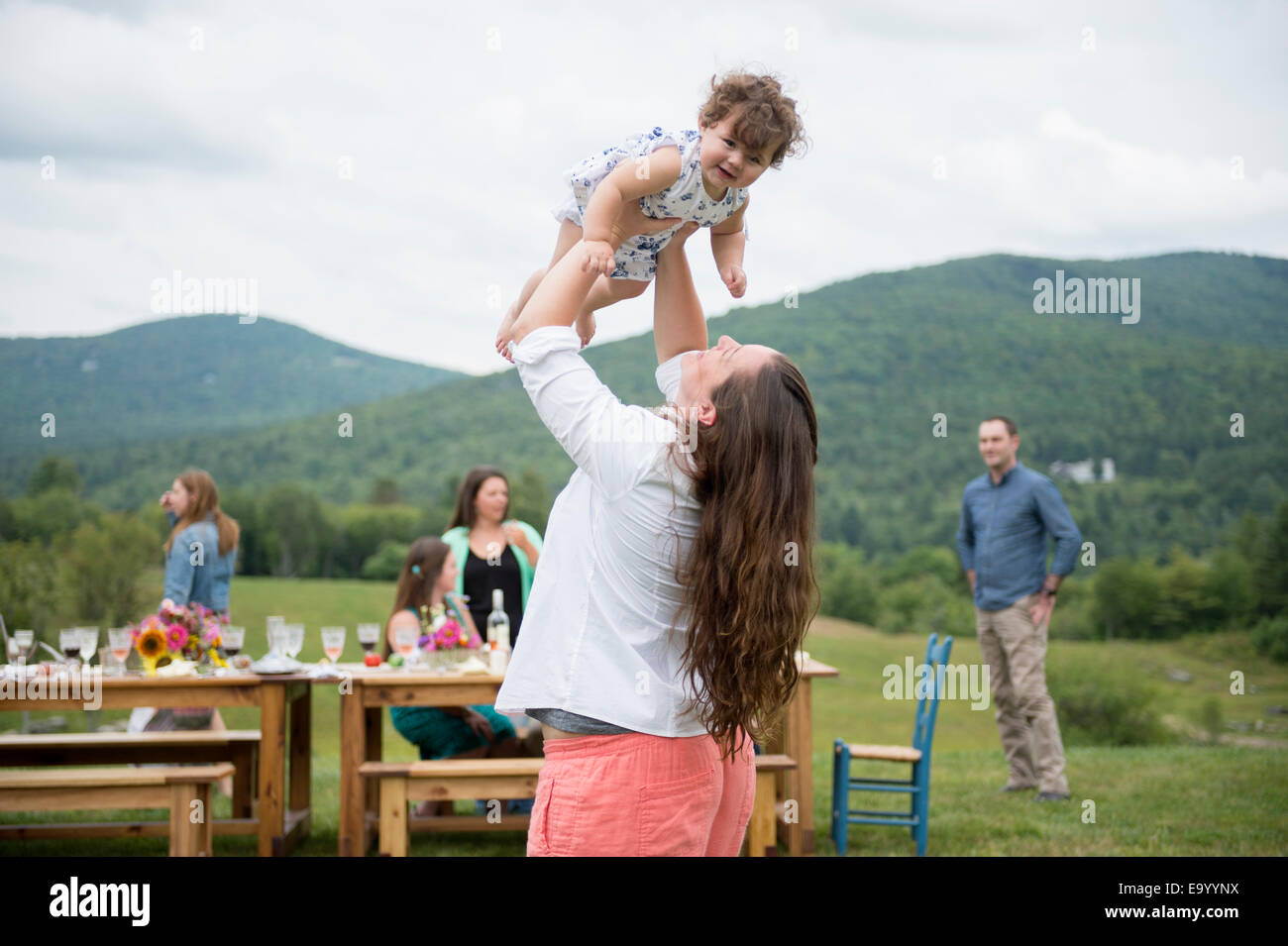 Mid adult woman holding baby girl in air at family gathering, outdoors - Stock Image