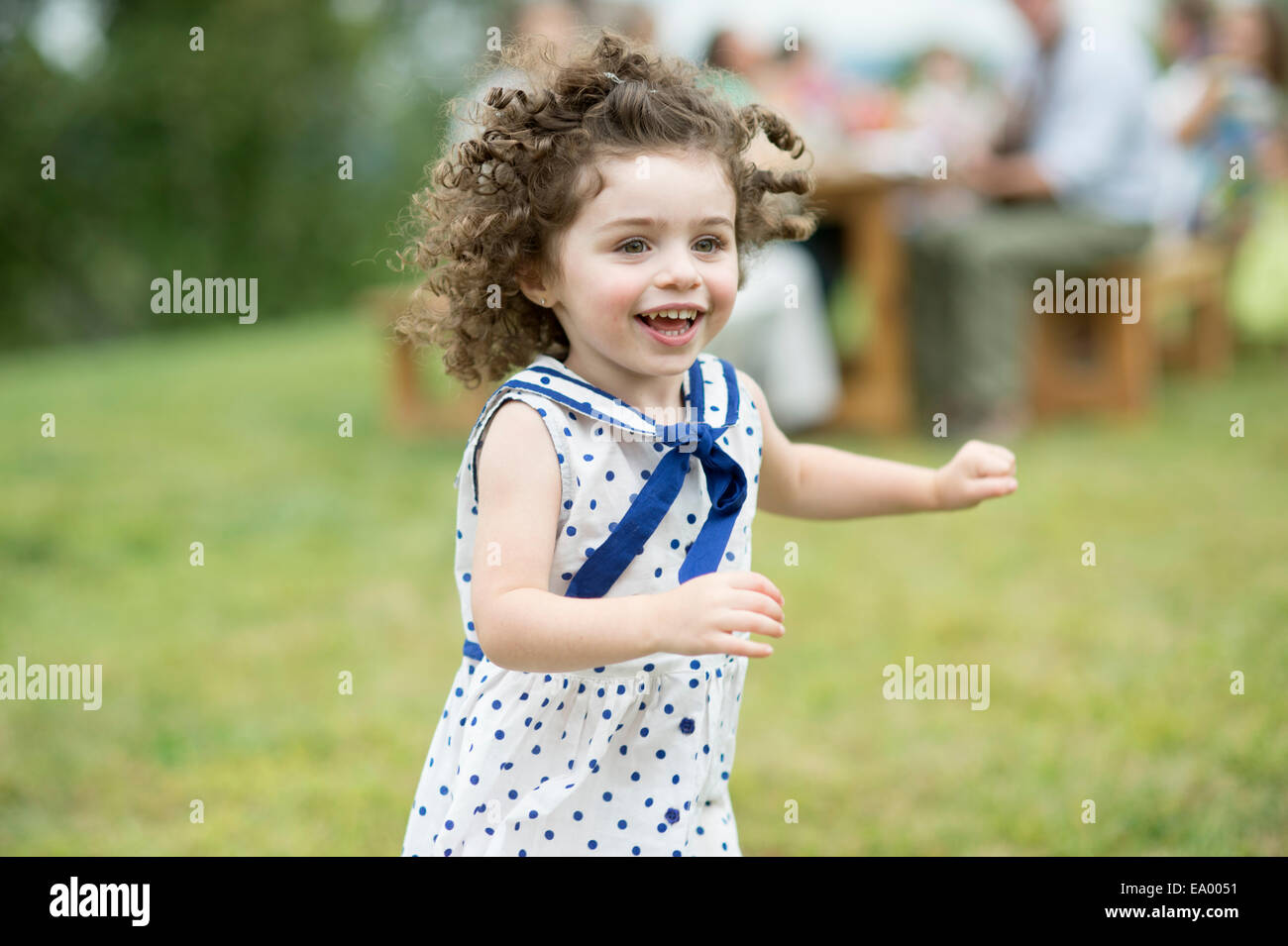 Young girl running and playing at family gathering - Stock Image