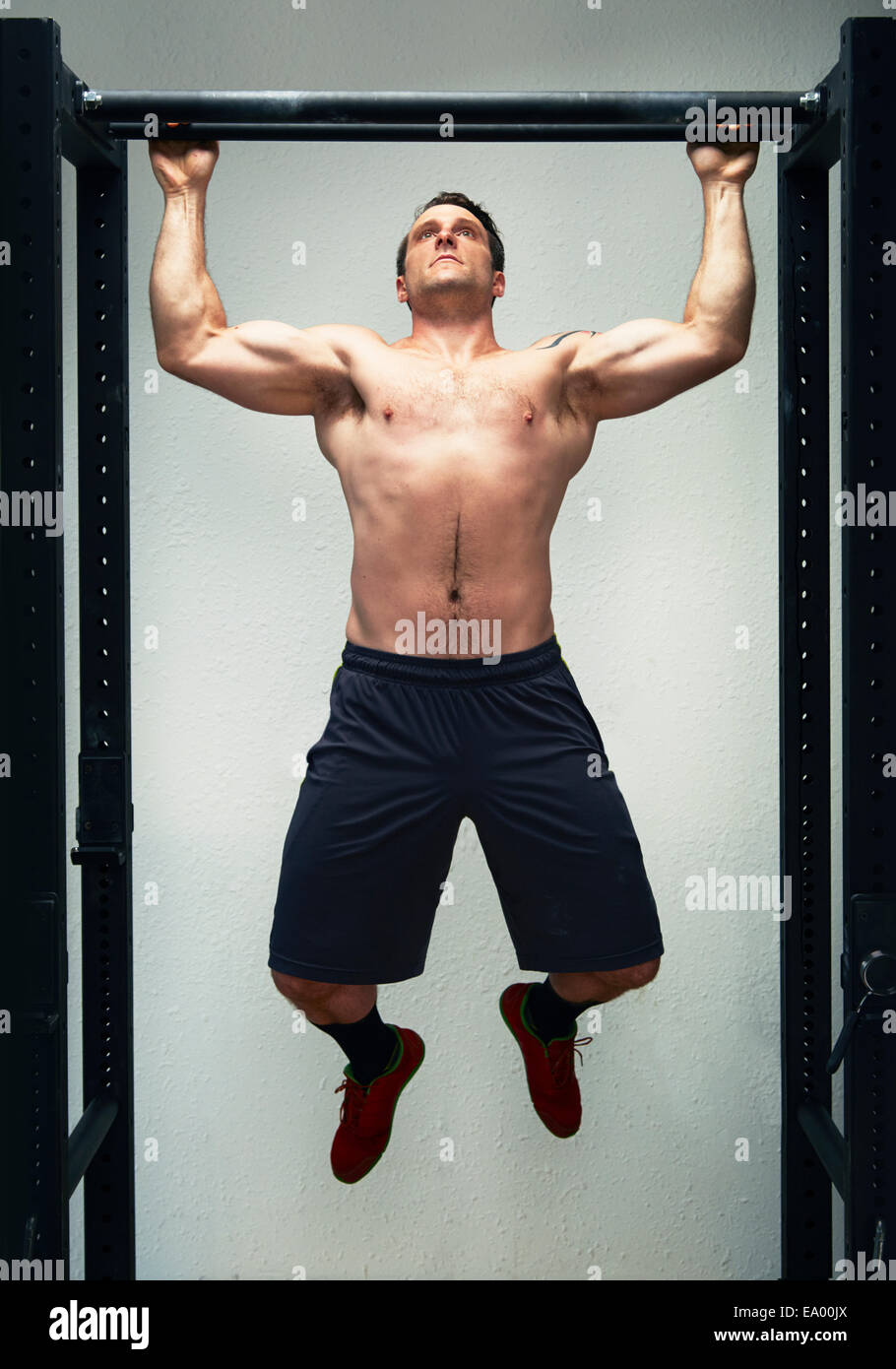 Mid adult male doing pull ups on exercise bar in gym - Stock Image