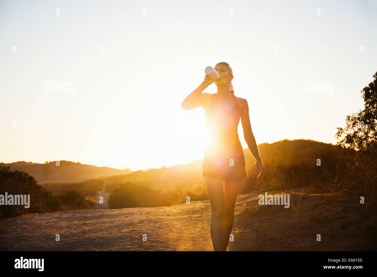 Female jogger drinking in sunlight, Poway, CA, USA - Stock Image