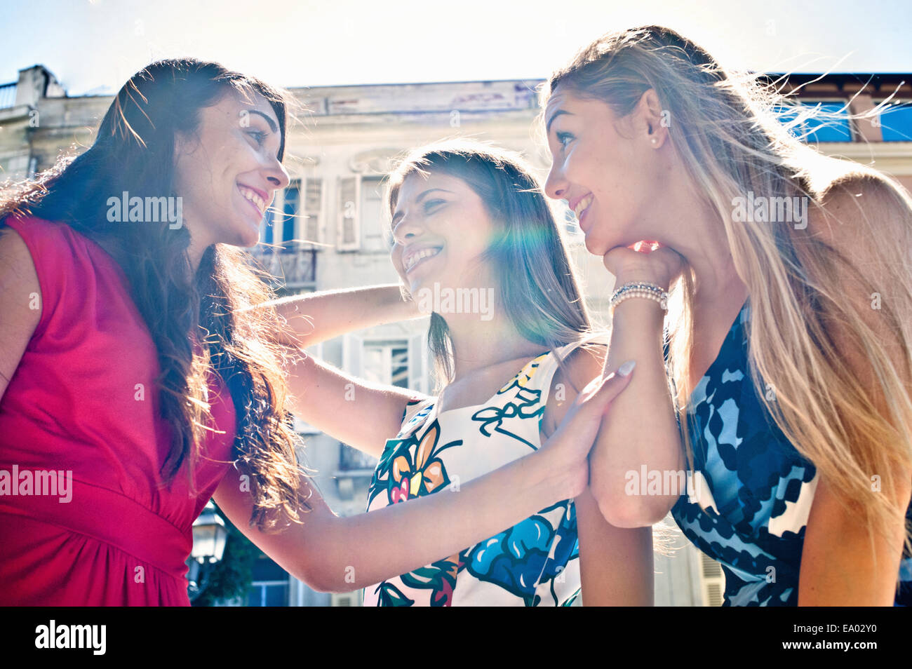 Three young female friends chatting on street, Cagliari, Sardinia, Italy - Stock Image