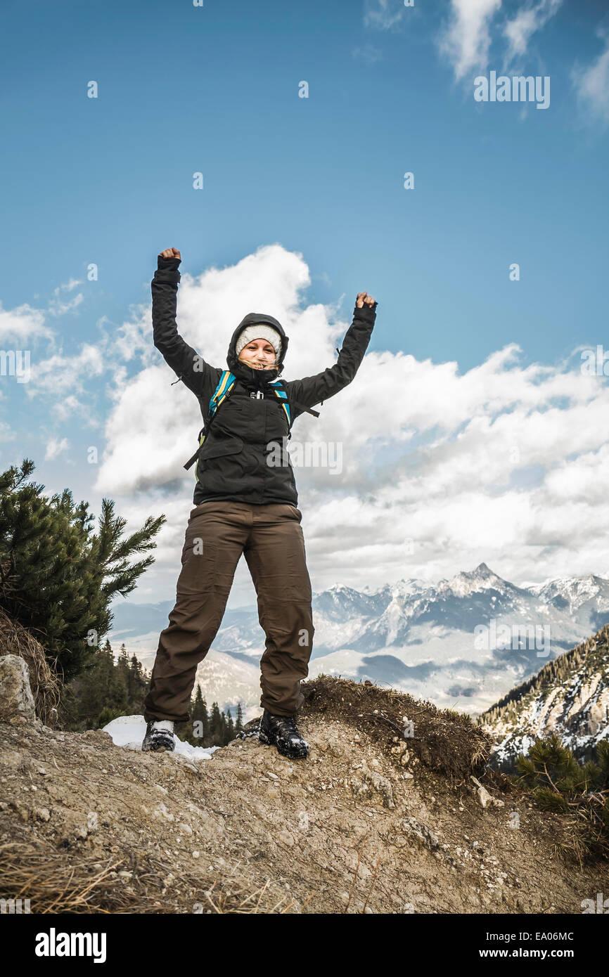 Young woman celebrating on mountain ridge, Hundsarschjoch, Vils, Bavaria, Germany - Stock Image