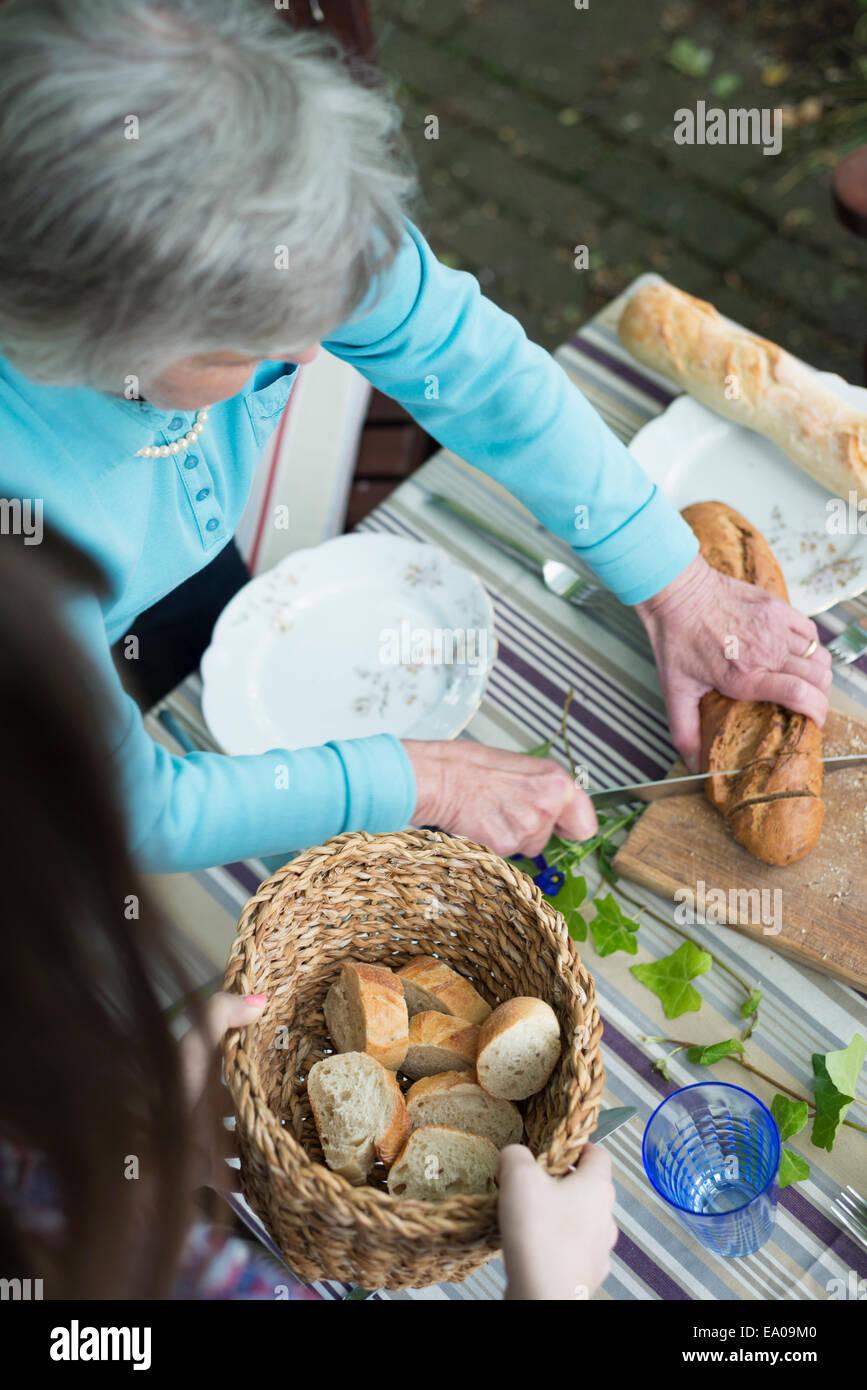 Senior woman cutting bread, high angle - Stock Image