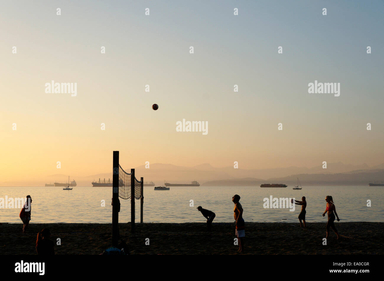 People playing beach volleyball at sunset, Kitsilano Beach, Vancouver, British Columbia, Canada Stock Photo