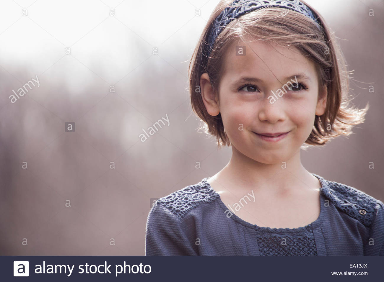 Portrait of pretty girl looking away and smiling - Stock Image