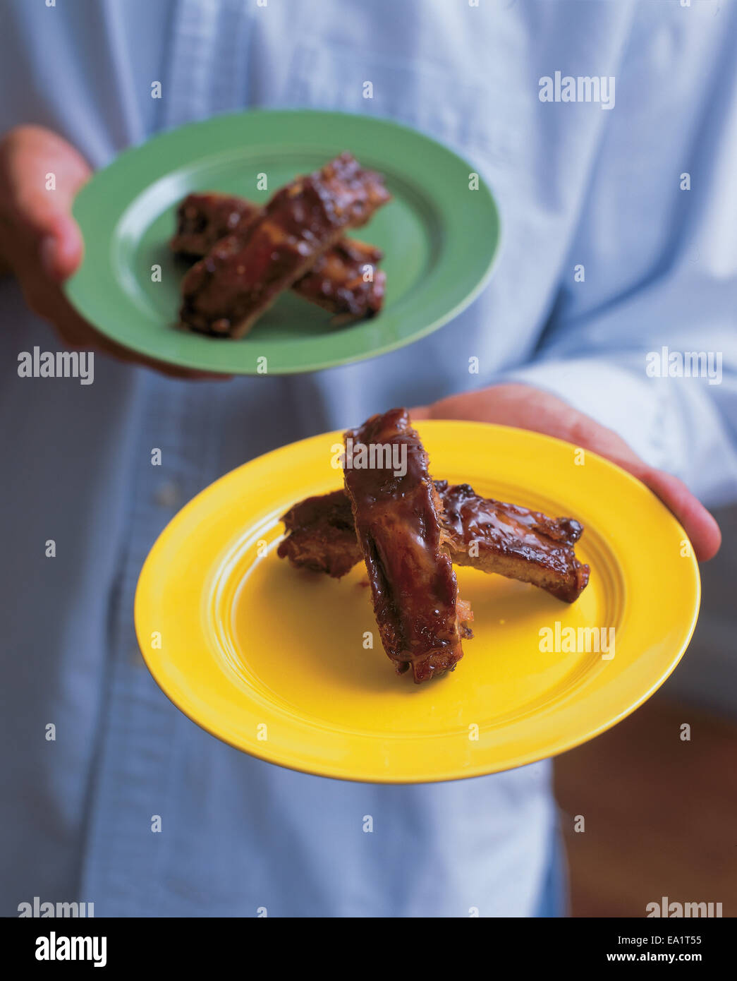 ribs on plate being handed out - Stock Image