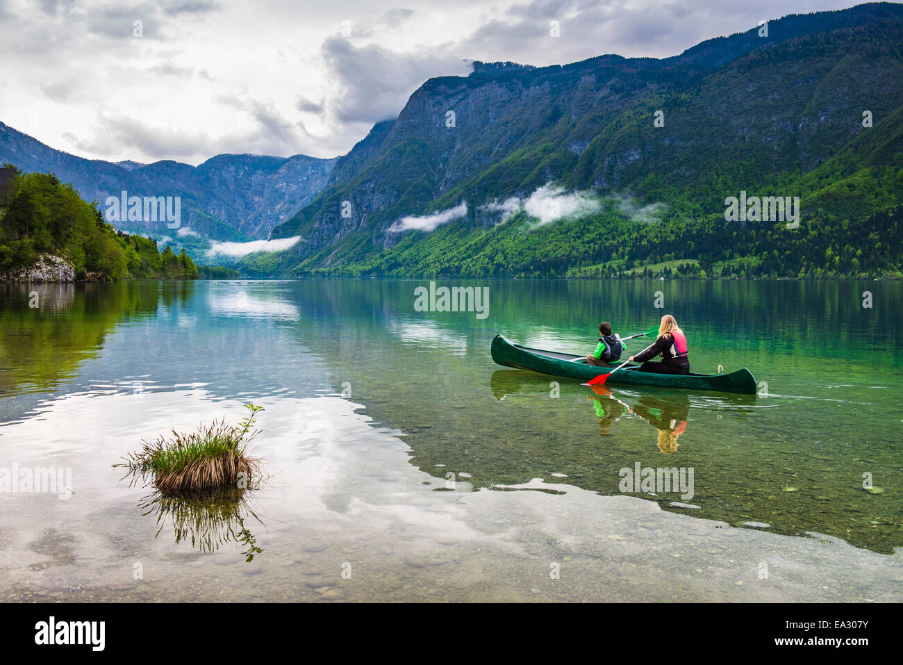 Mother and son canoeing on Lake Bohinj, Triglav National Park, Julian Alps, Slovenia, Europe - Stock Image