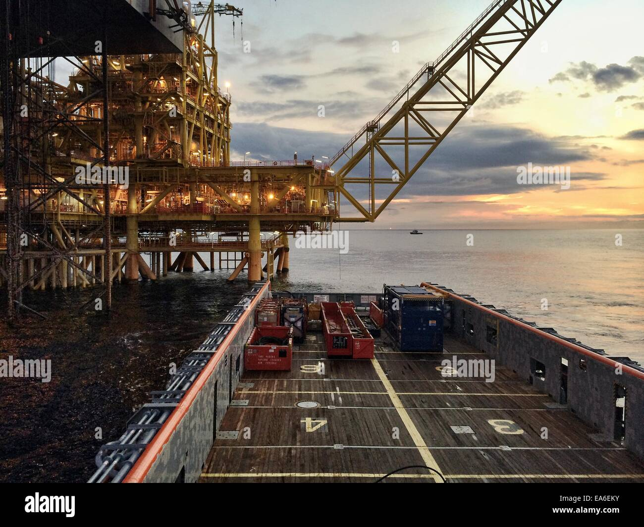 Central processing oil platform on cargo operation with offshore vessel at sunrise - Stock Image