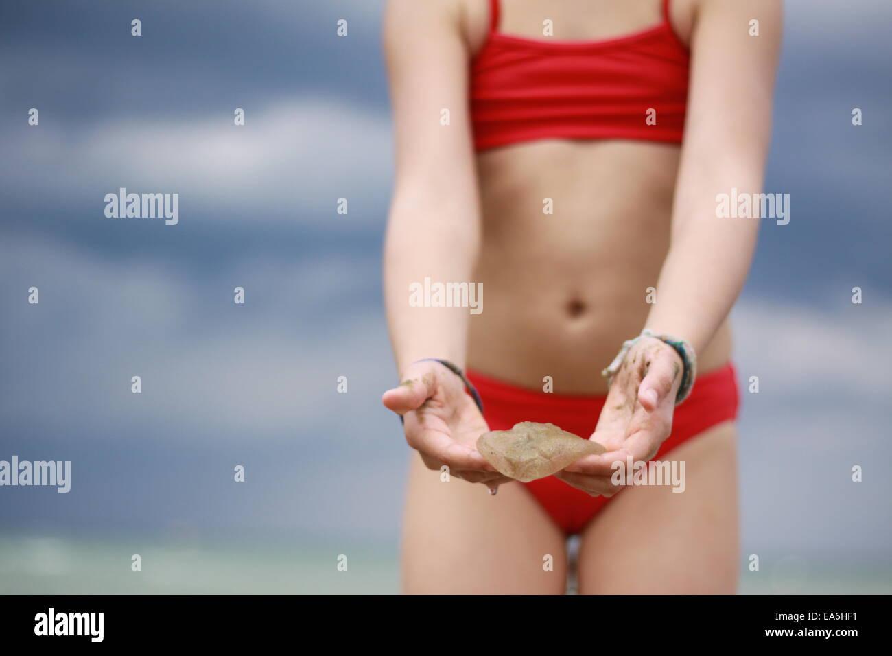 Girl (12-13) holding jellyfish - Stock Image
