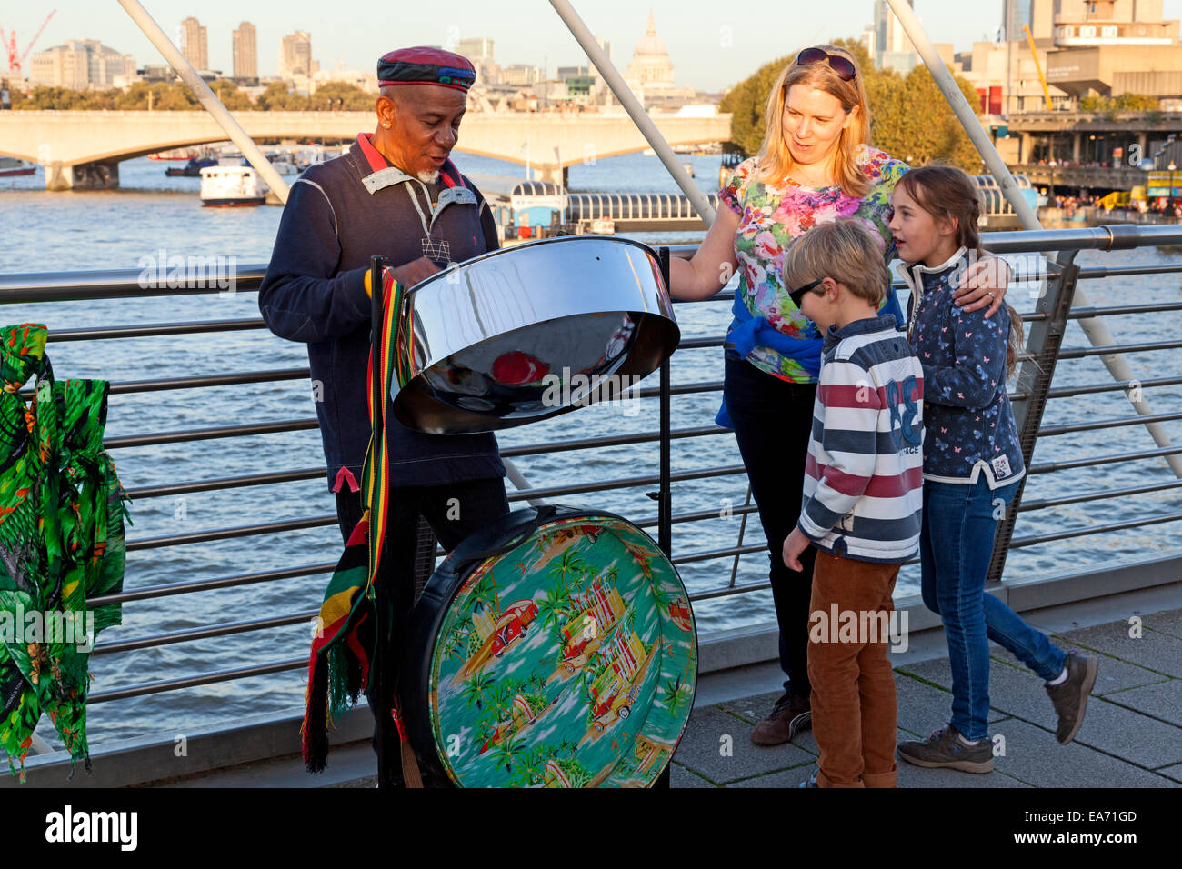 steel-drummer-playing-for-two-children-on-the-golden-jubilee-bridge-EA71GD.jpg