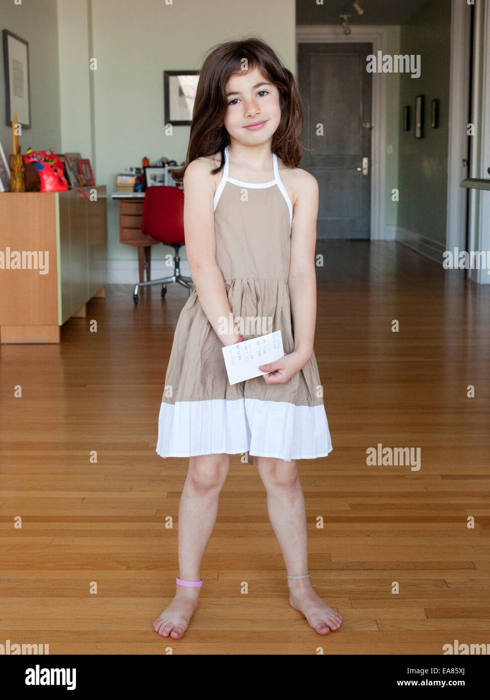 young girl in dress at home - Stock Image