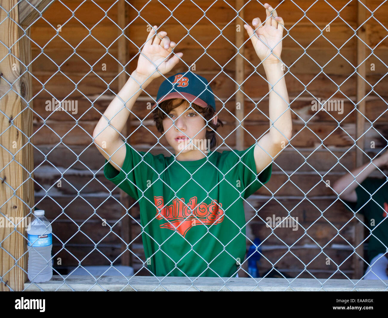youth baseball player in dugout - Stock Image