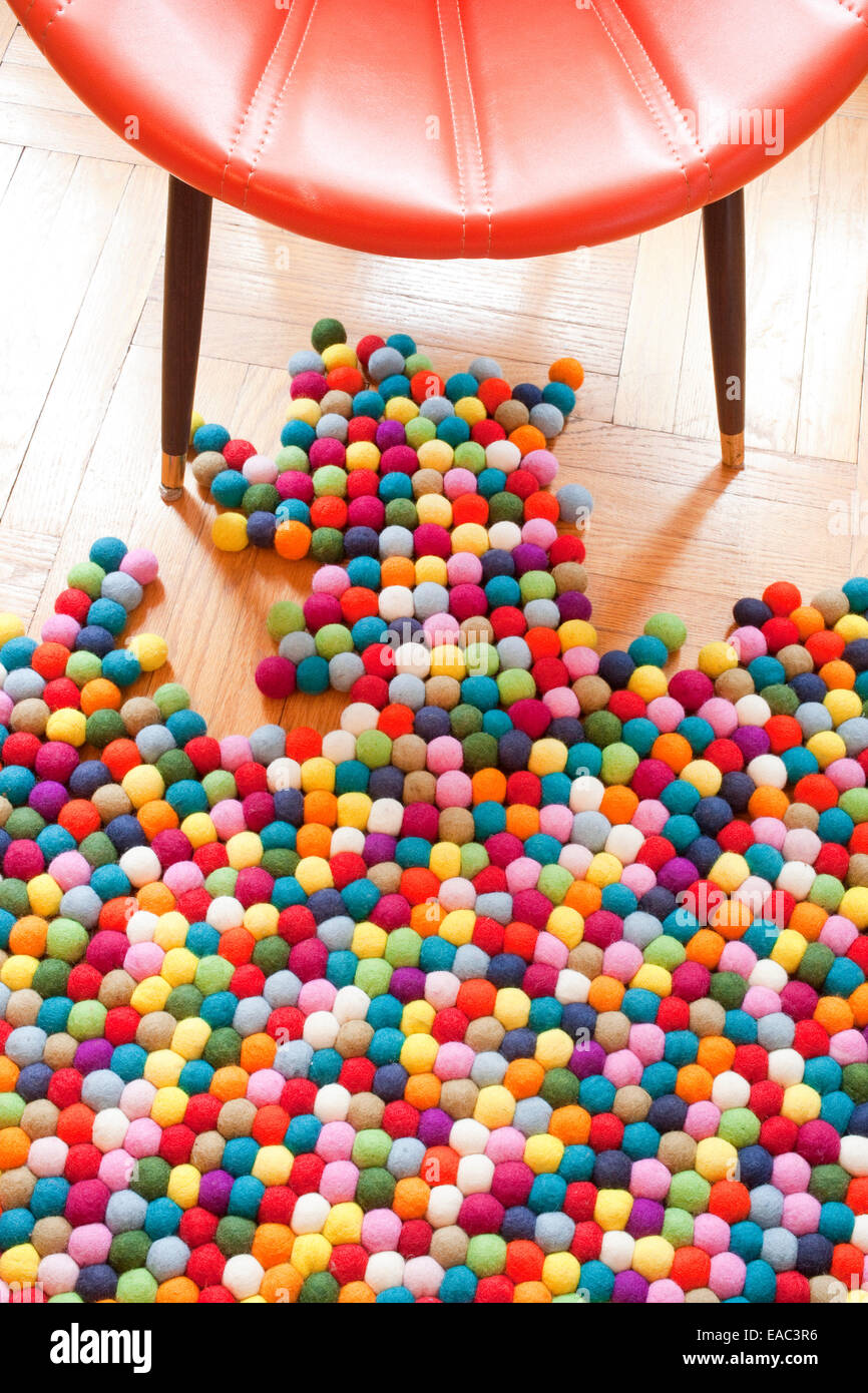 Colorful Rug and chair on wood floor - Stock Image
