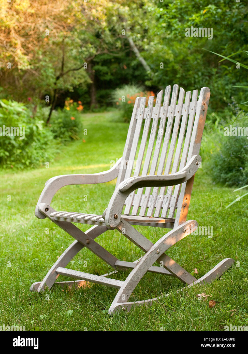 antique wooden rocking chair on lawn and country lane - Stock Image