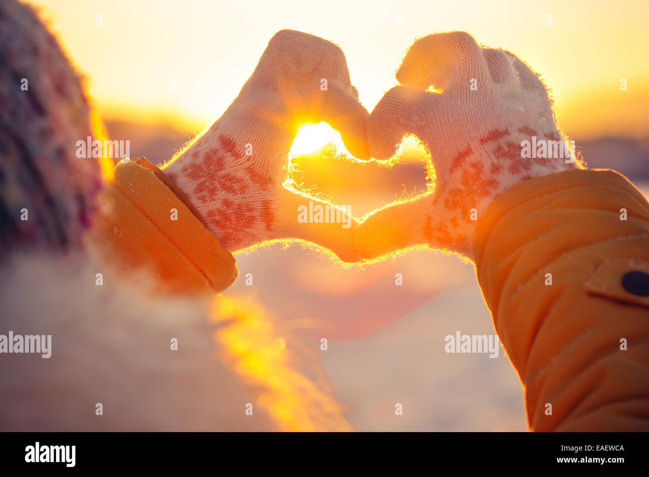 Woman hands in winter gloves Heart symbol shaped Lifestyle and Feelings concept with sunset light nature on background - Stock Image