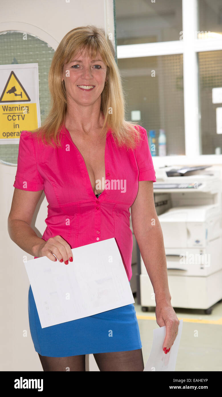secretary wearing short skirt and low cut shirt with paperwork from