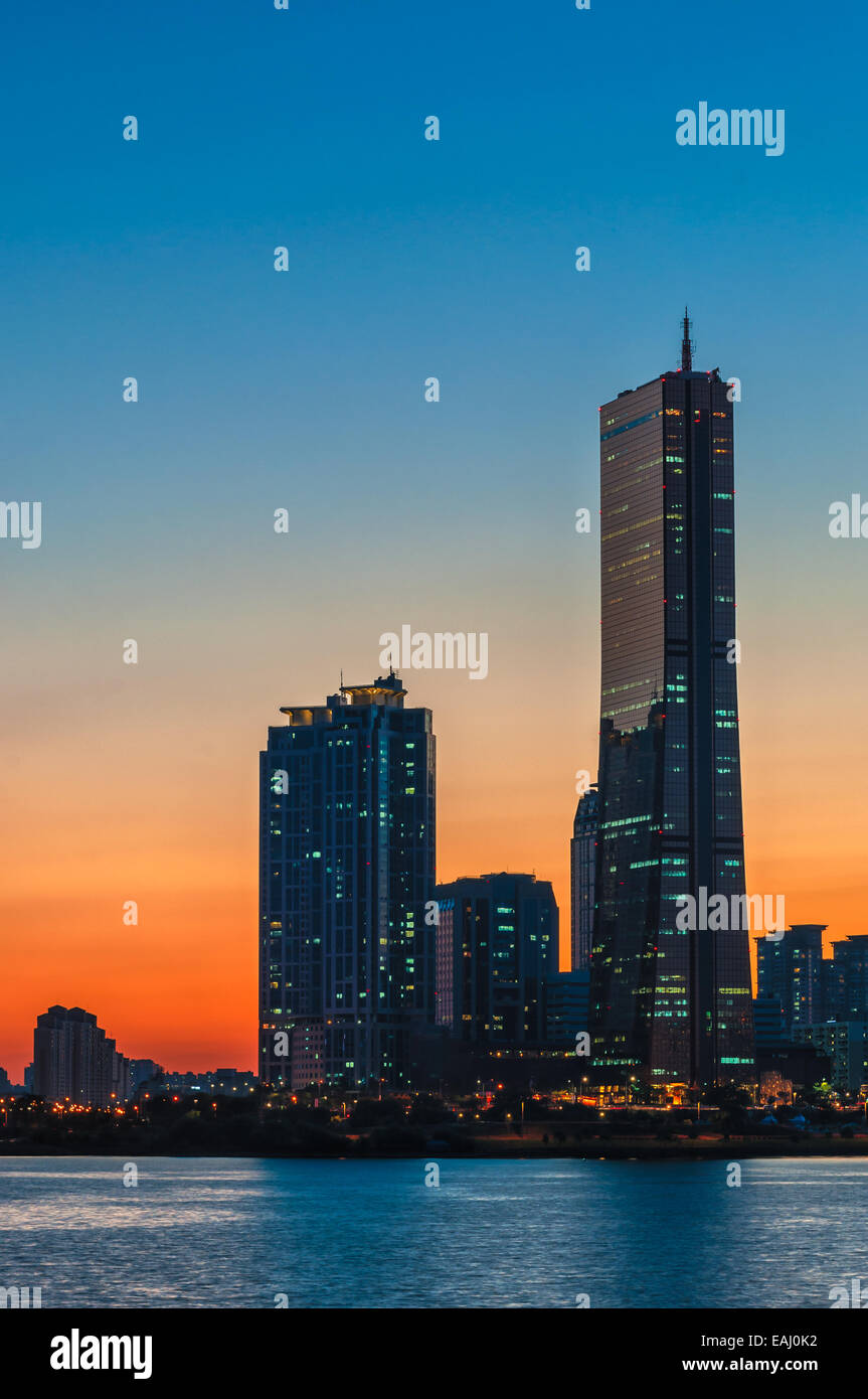 The sun sets behind the skyscrapers of Seoul, South Korea. - Stock Image