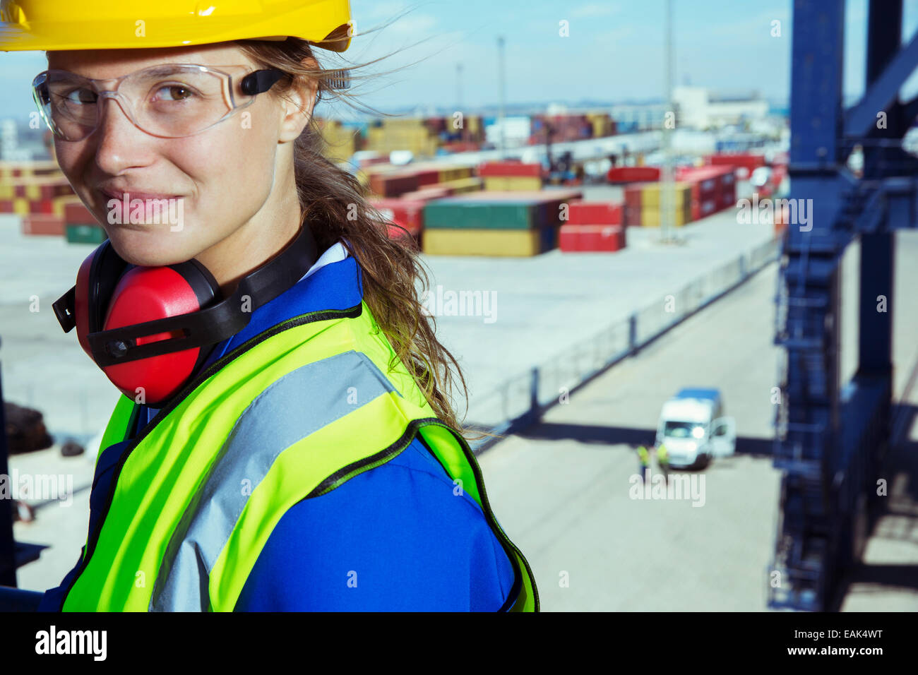 Worker smiling near cargo containers - Stock Image