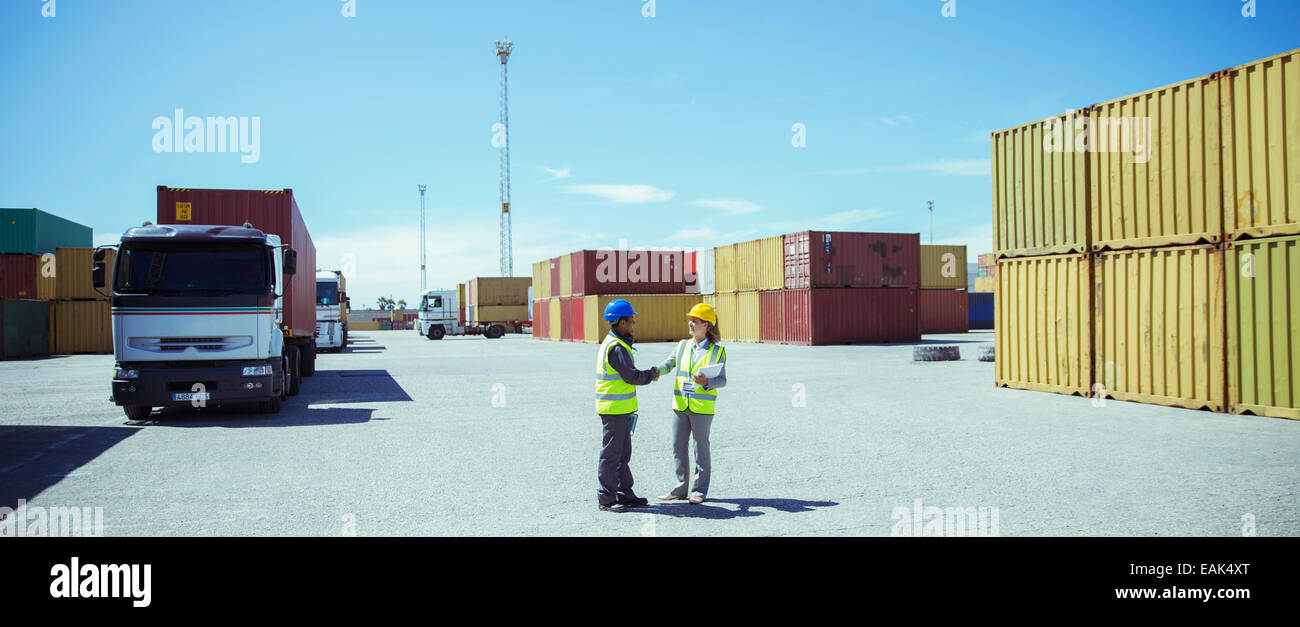 Workers talking near cargo containers - Stock Image