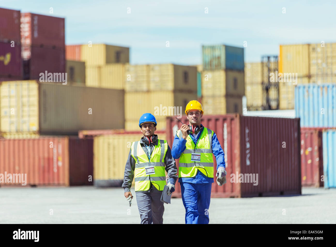 Worker and businessman walking near cargo containers - Stock Image