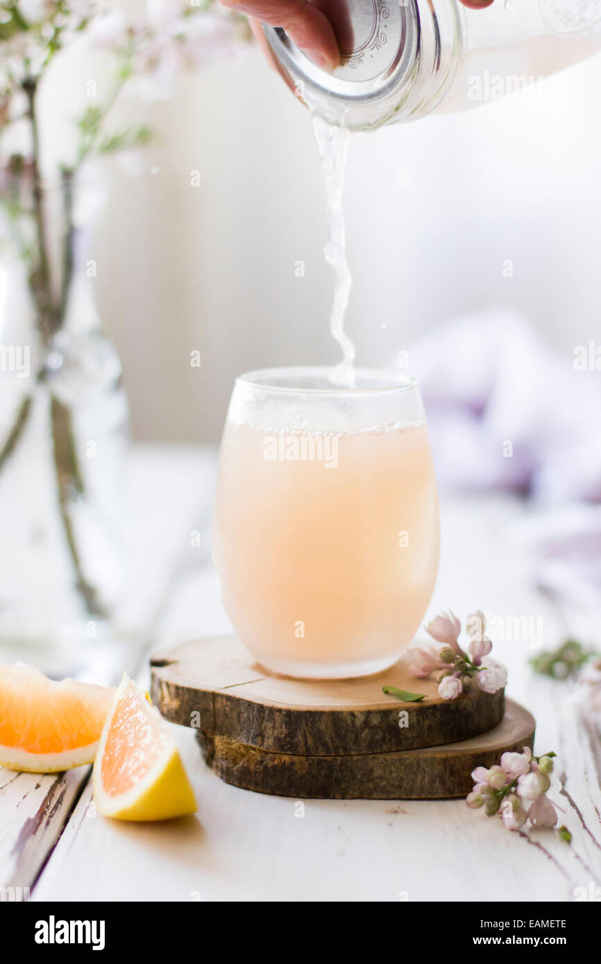 Pink Grapefruit Cocktail Pouring into Glass, with Flowers on White Wood - Stock Image