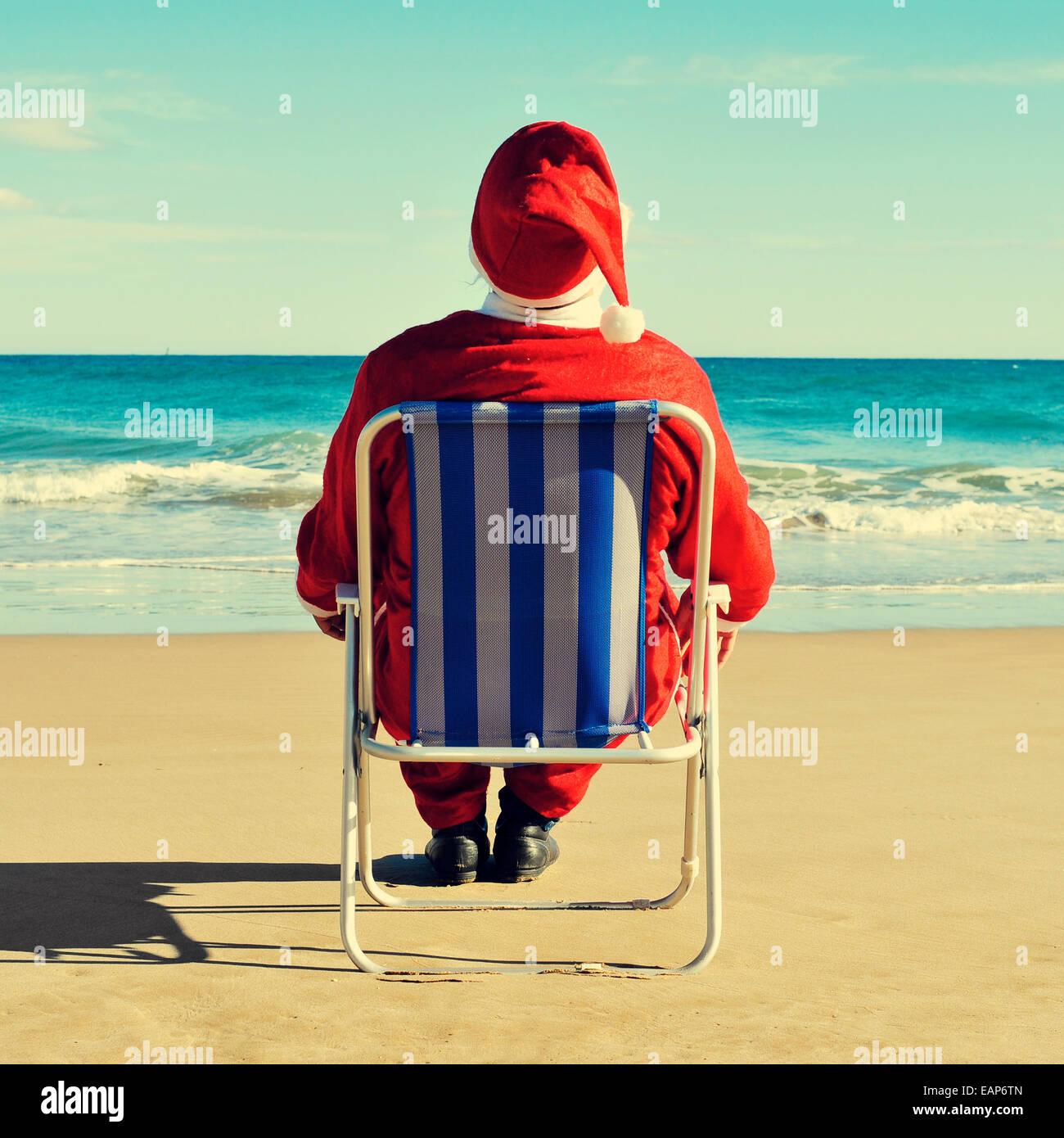 santa claus sitting in a beach chair on the beach - Stock Image