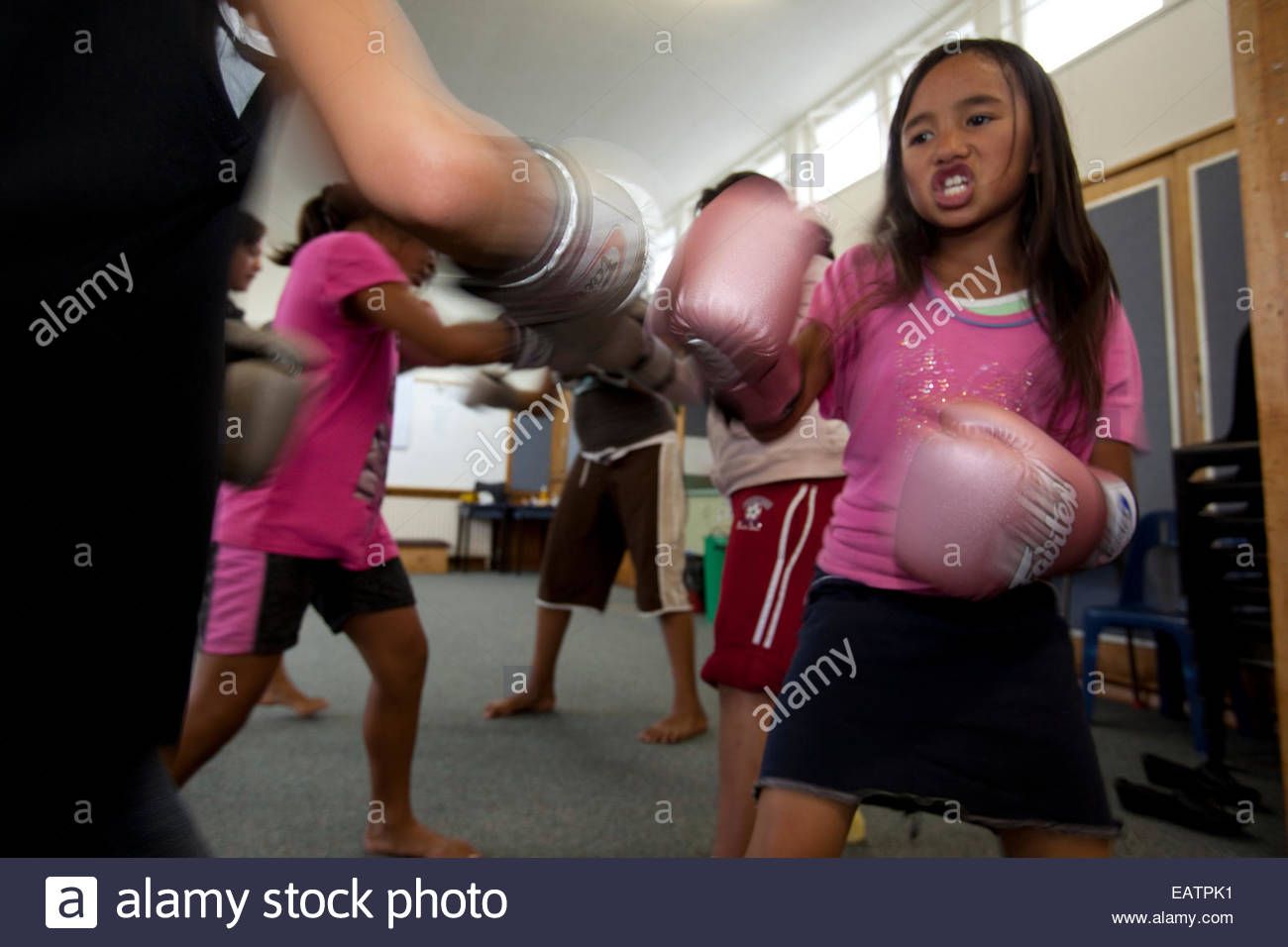 A young Maori girl practices boxing. - Stock Image