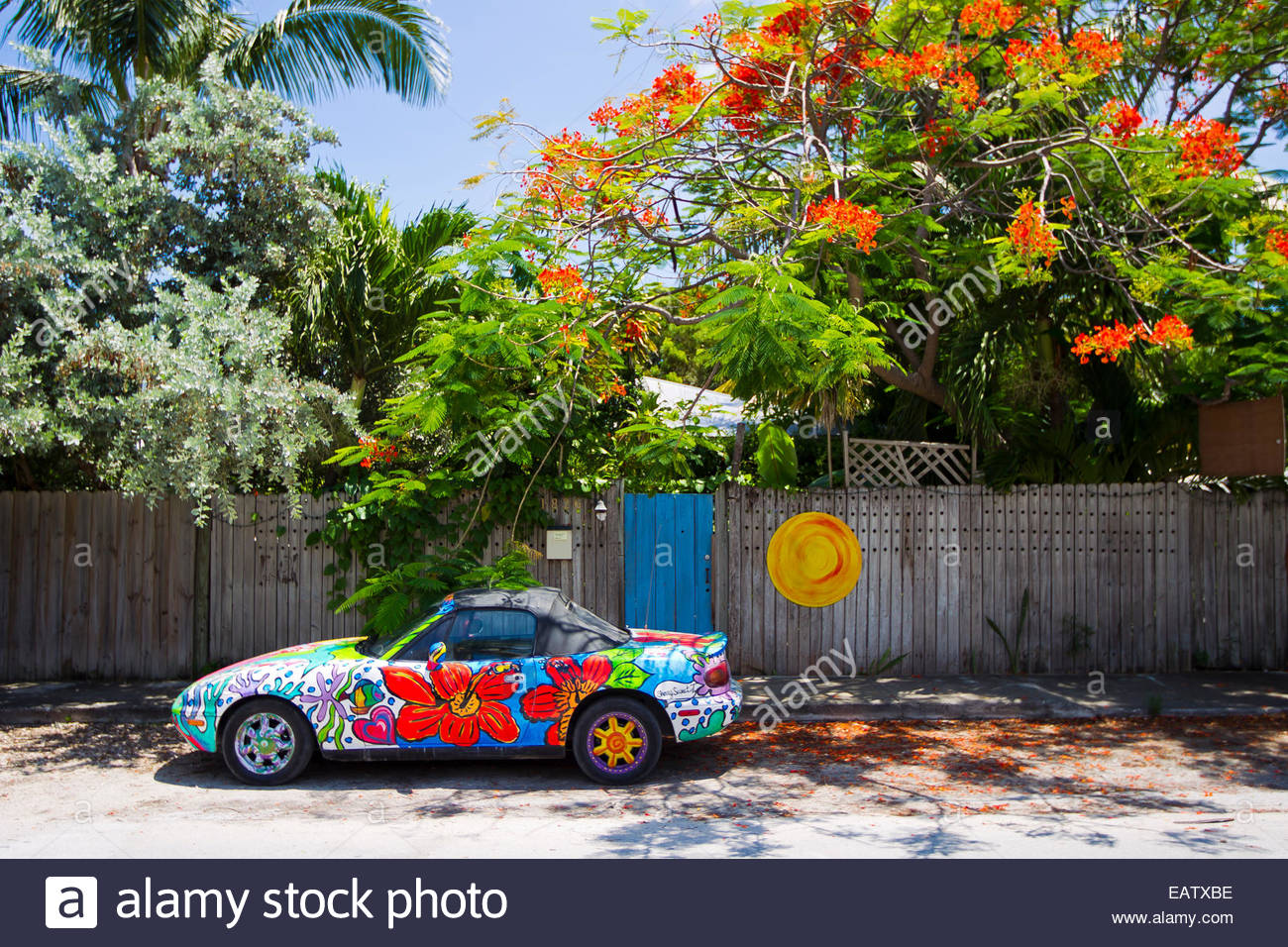 A colorful painted car with flowers is parked on the side walk next ...