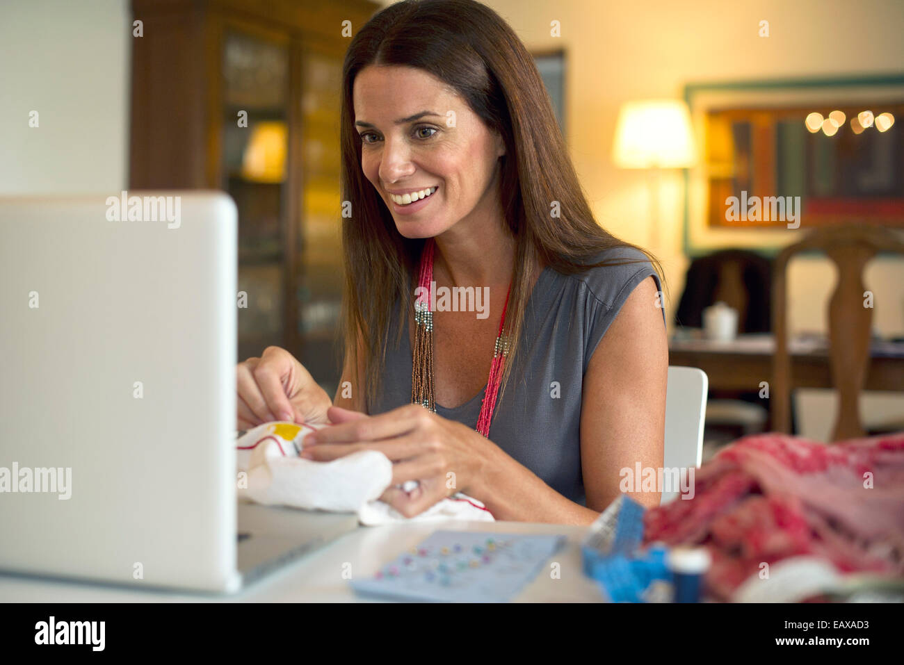 Woman looking at laptop computer while sewing - Stock Image