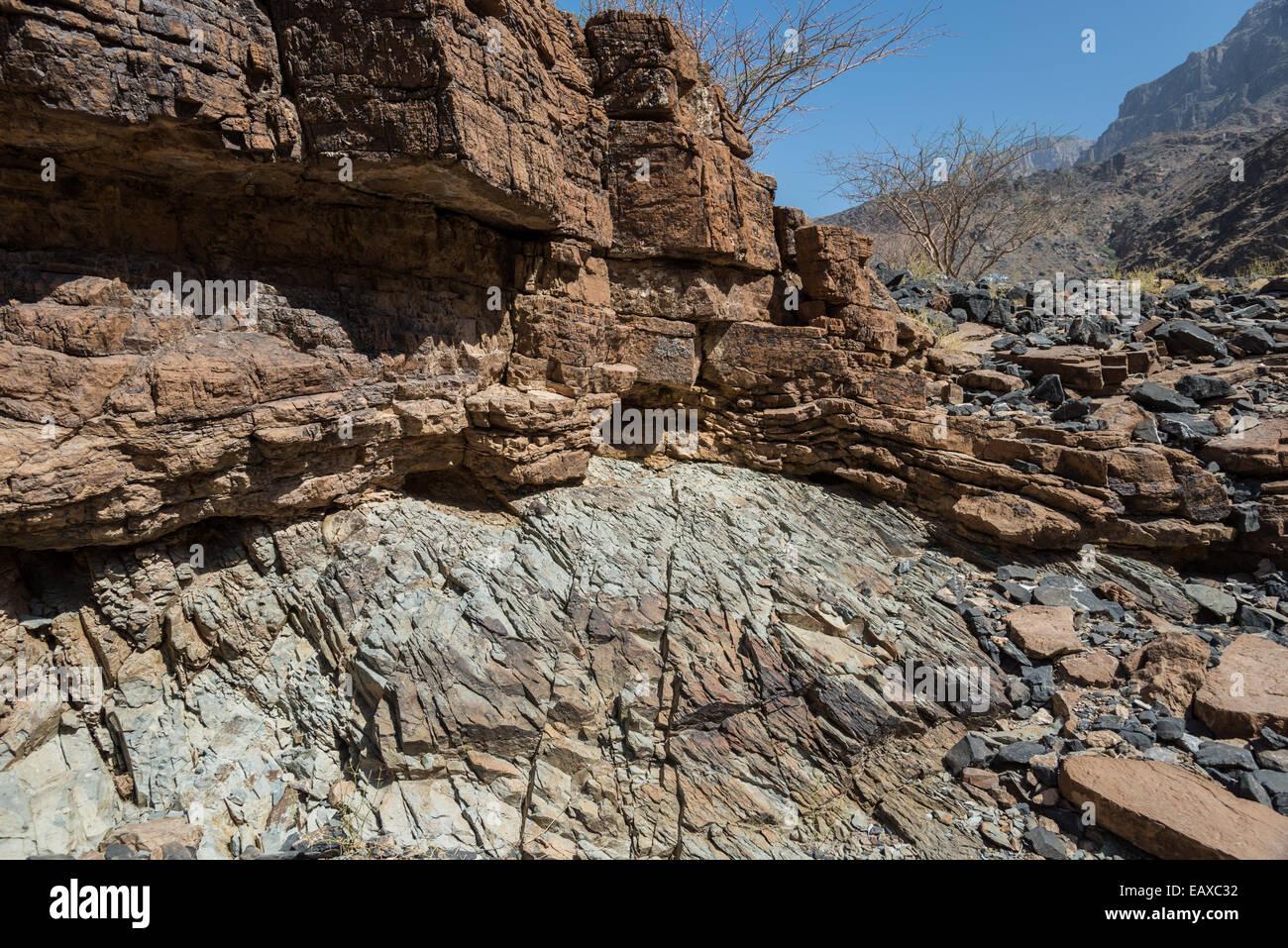 An angular unconformity between gray mudstone and brown dolostone. Oman. - Stock Image