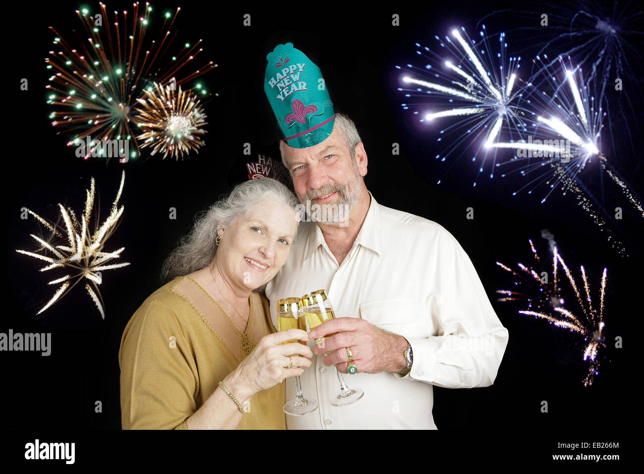 beautiful senior couple celebrating a happy new year with a champagne toast while fireworks go off in the background