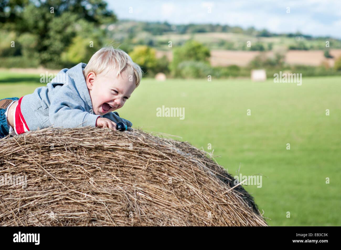 Boy crawling on hay bale laughing - Stock Image