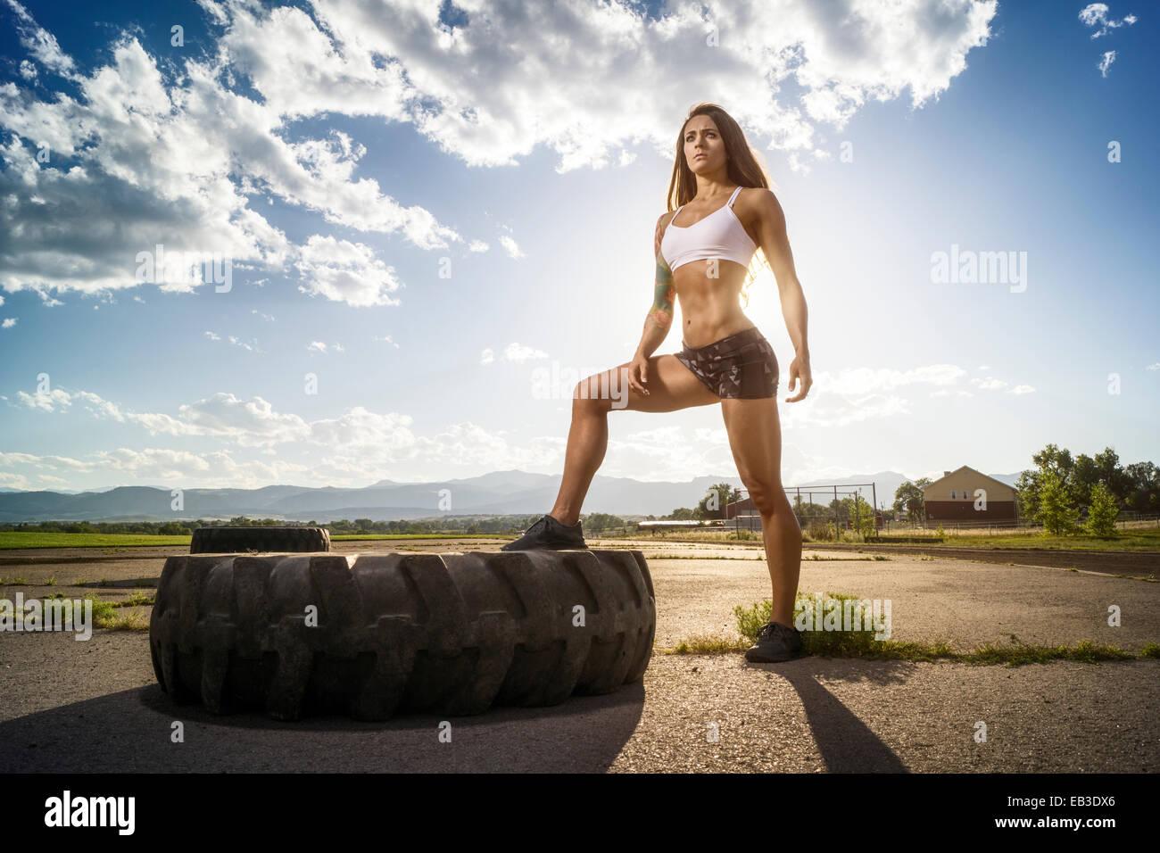 USA, Colorado, Jefferson County, Arvada, Female athlete posing with track tire - Stock Image