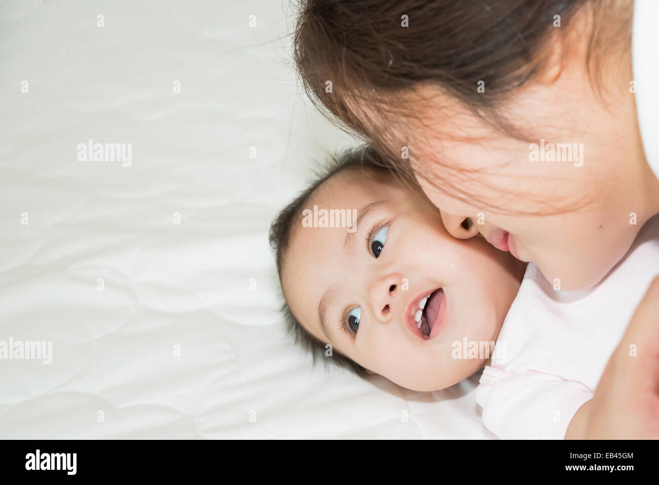 Happy cheerful family. Asian mother and baby kissing, laughing and hugging - Stock Image