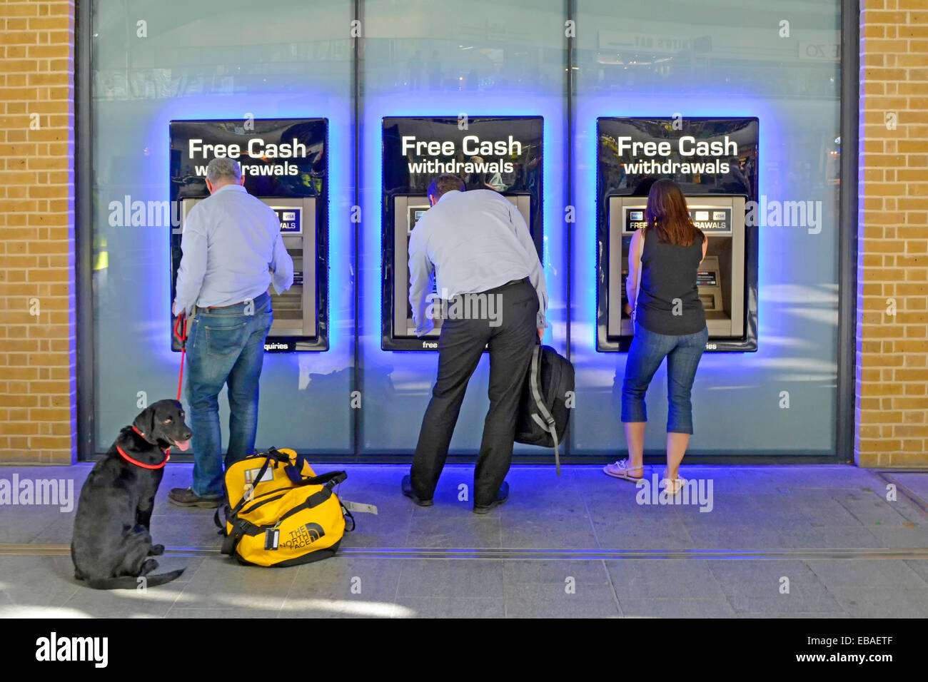 Dog with owner and two other people using atm machines at railway station Stock Photo
