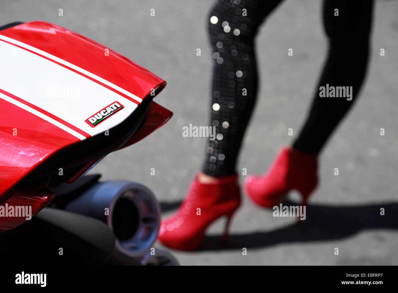 Ducati motorcycle detail with a woman's legs wearing red high heels in the background Stock Photo