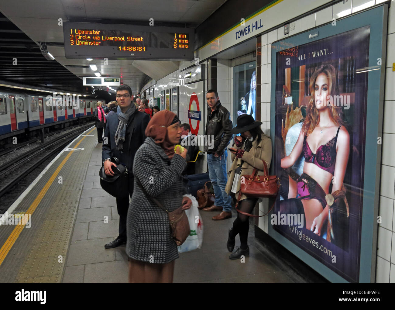 City Underground platform,England,UK,GB,Great,Britain,transport,people,looking,at,a,poster,fun,shot,LU,circle,district,line,flesh,underwear,bra,stockings,suspenders,rude,Muslim,woman,lady,culture,clash,islam,gotonysmith