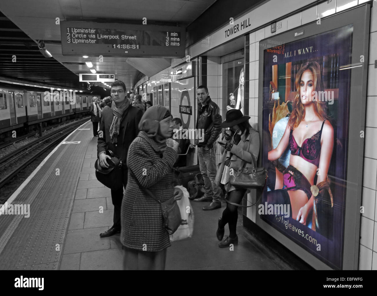 City Underground platform,England,UK,GB,Great,Britain,transport,people,looking,at,a,poster,fun,shot,LU,circle,district,line,flesh,underwear,bra,stockings,suspenders,in,selective,color,colour,muslim,woman,lady,culture,clash,Islam,dumbfounded,gotonysmith,Buy Pictures of,Buy Images Of