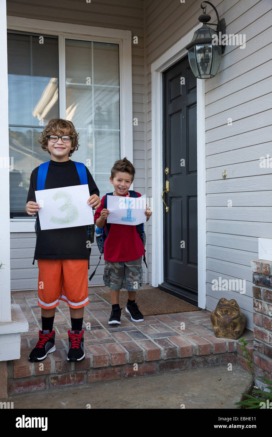 Portrait of two brothers holding up pieces of paper with 3 & 1 - Stock Image