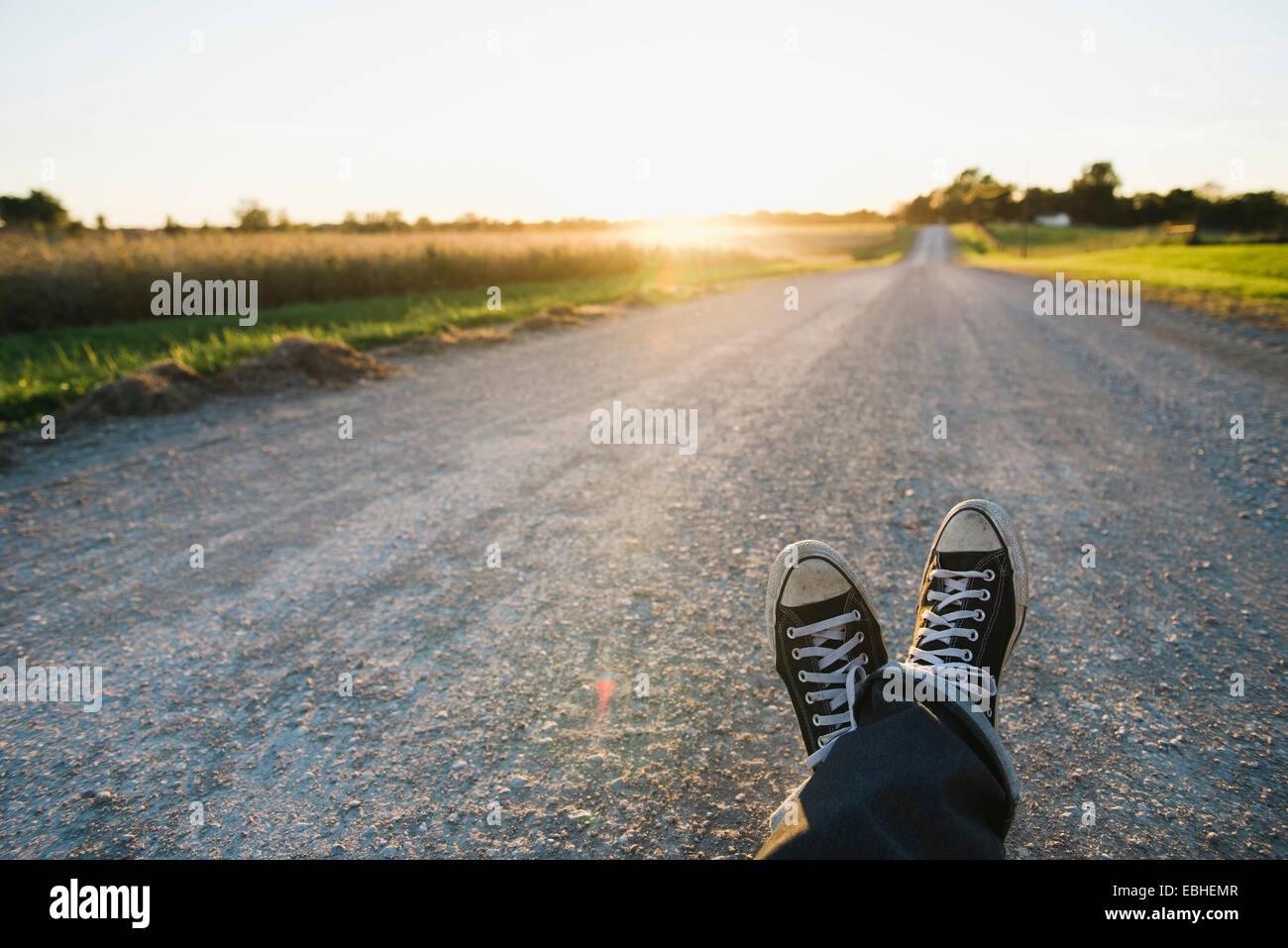 Feet of farmer traveling on rural road at dusk, Plattsburg, Missouri, USA - Stock Image