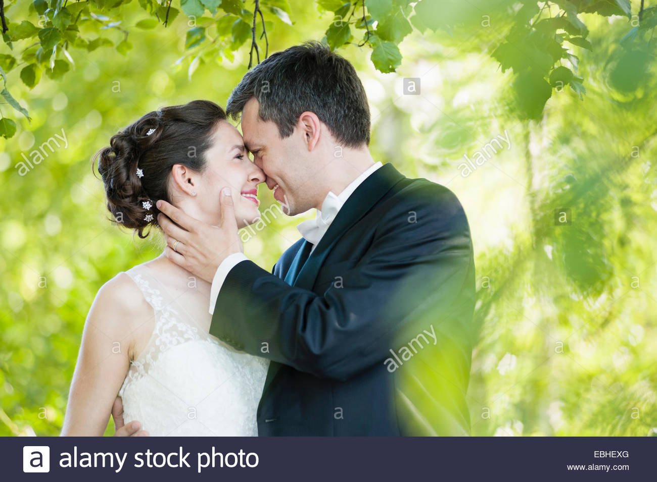 Romantic newlywed mid adult couple face to face in park foliage - Stock Image