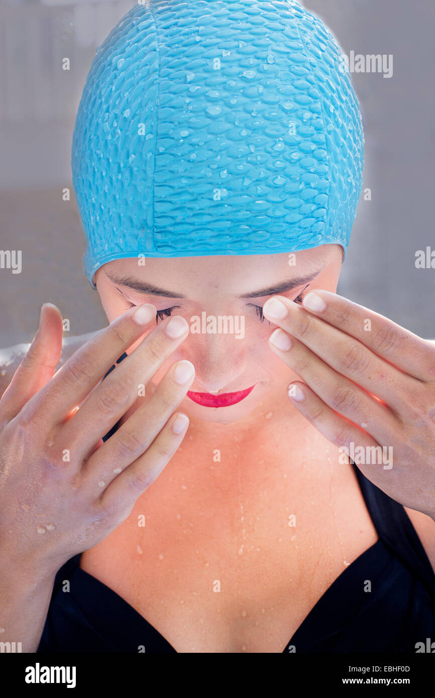 Close up portrait of young woman in swimming cap with hands over eyes - Stock Image