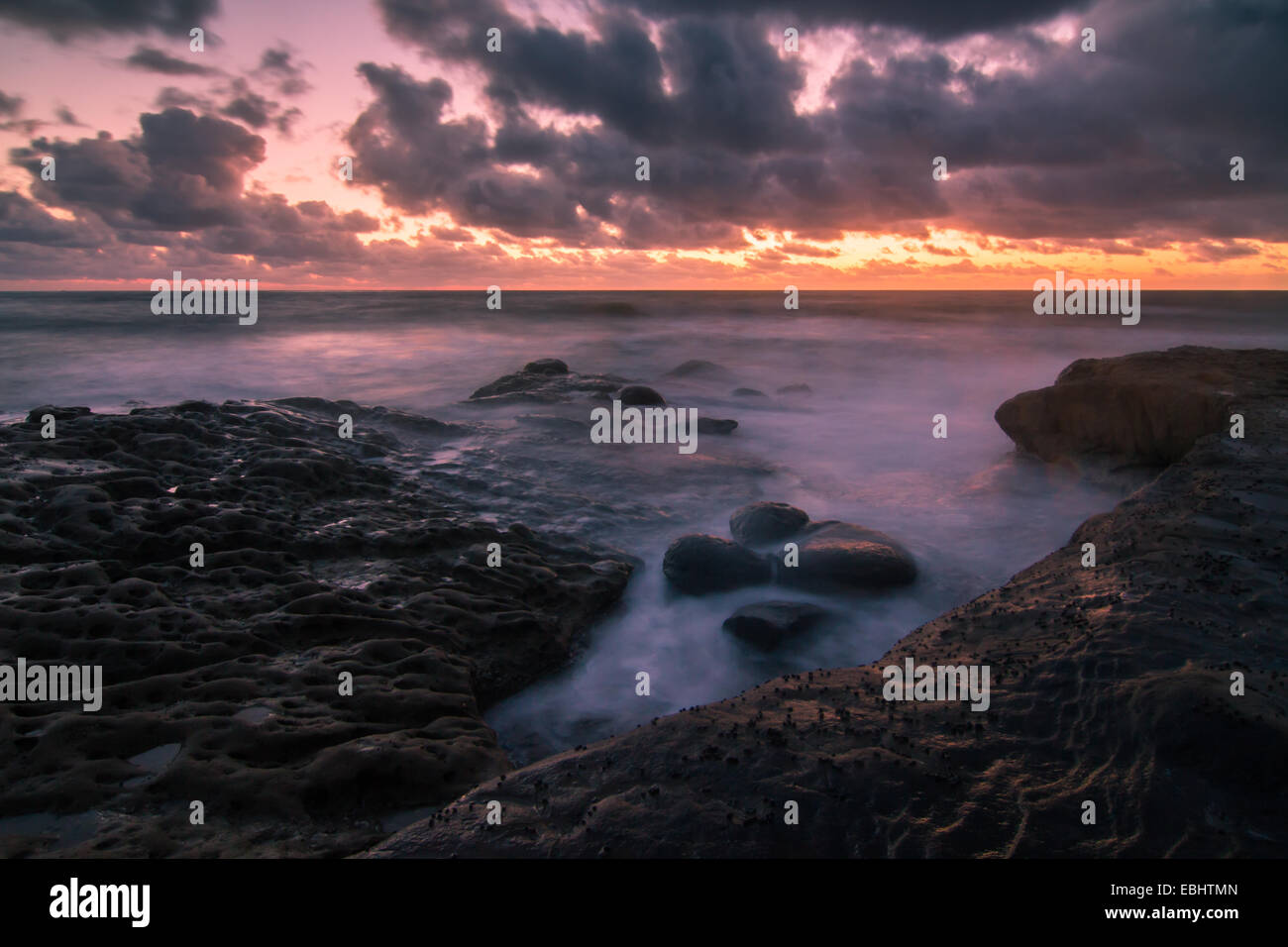 Surreal surf and rocks caught in a long exposure at sunset near San Diego, California Stock Photo