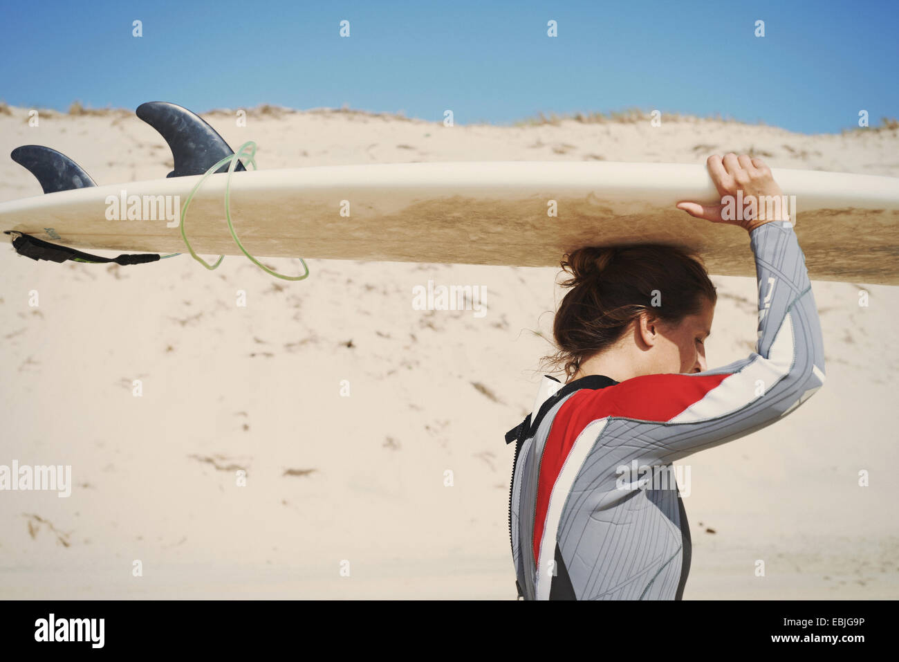 Surfer carrying surfboard on head at beach, Lacanau, France - Stock Image
