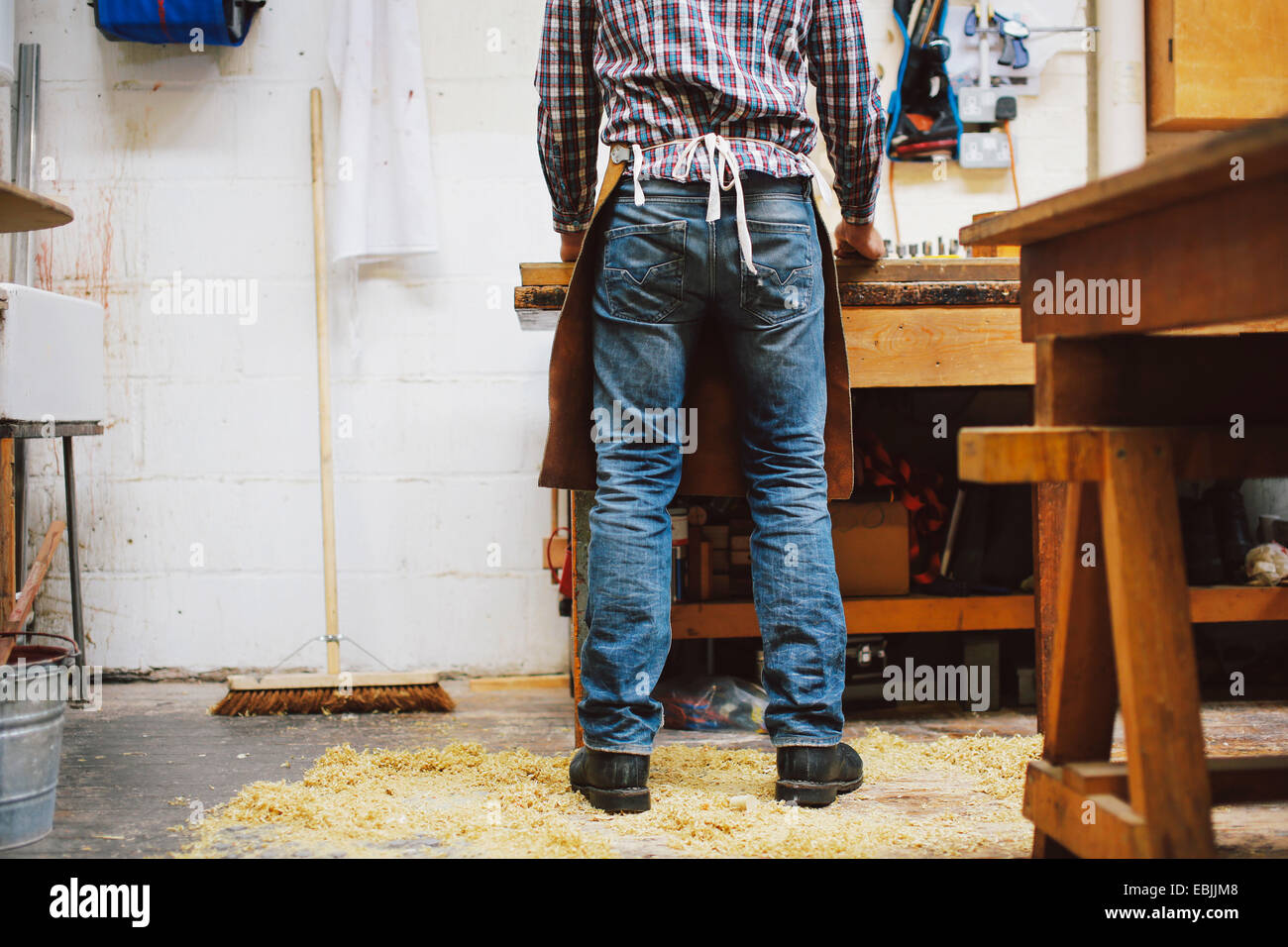 Cropped view of mature craftsman at workbench in pipe organ workshop - Stock Image
