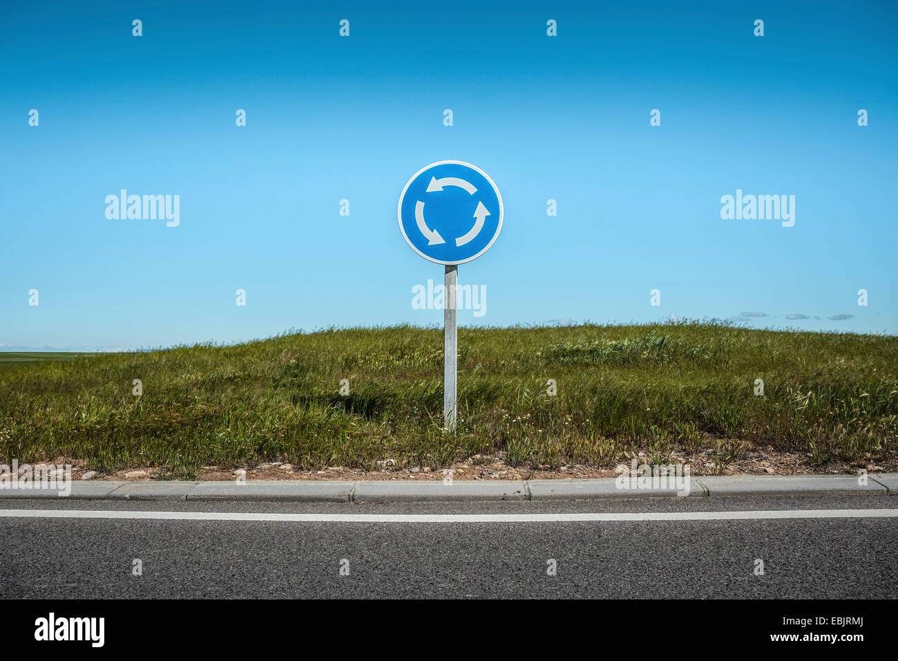 Roundabout sign by edge of road - Stock Image