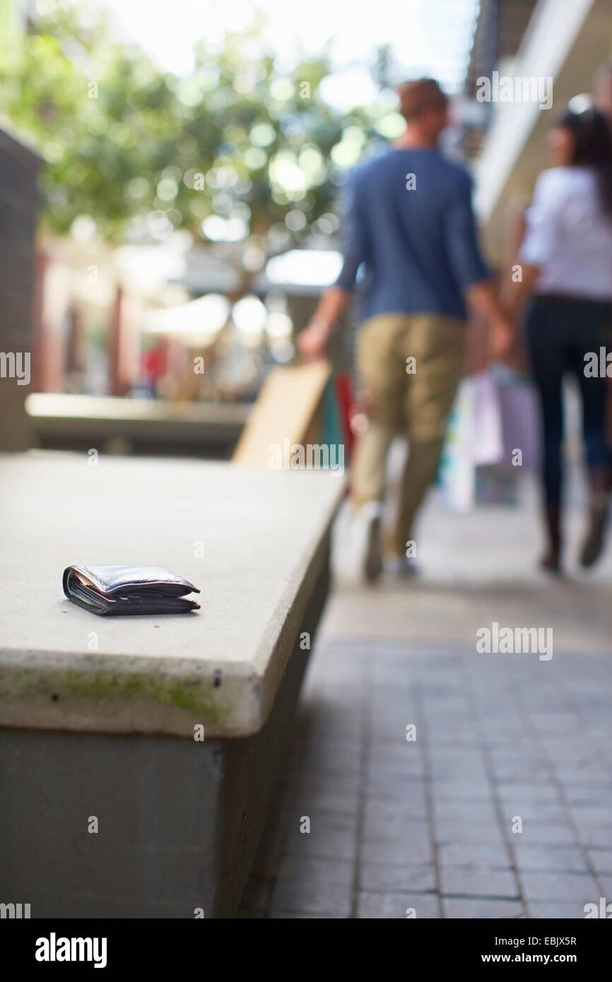 Mid adult couple walking with shopping bags, wallet left on seat behind them - Stock Image